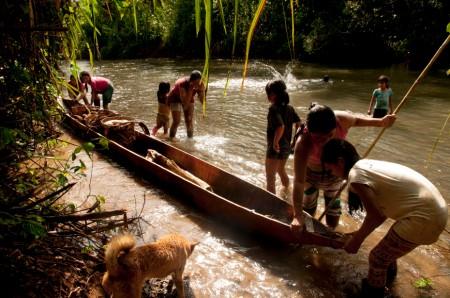Ena y sus hijas remontan el río Rotuno a tempranas horas de la mañana para ir a su chakra. /Foto: Esteffany Bravo S.